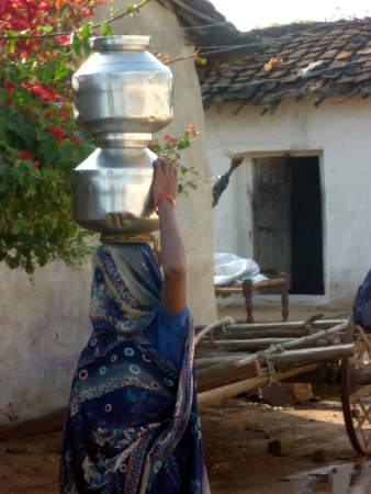 Traditional Indian woman carrying pots of water with her head fully covered