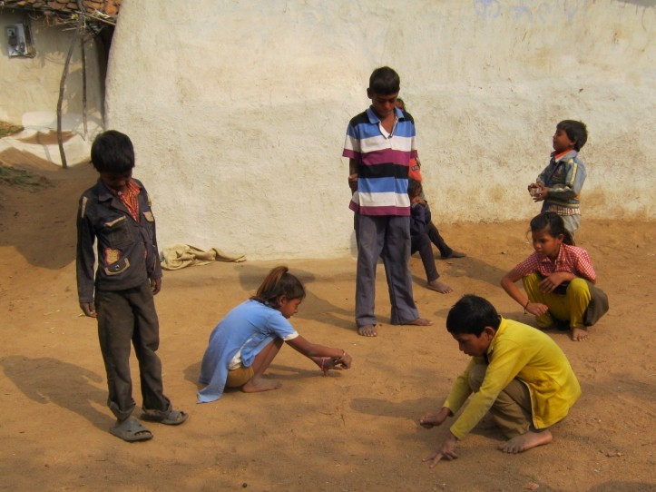 Girls and boys playing marbles together in a nearby village (2014)