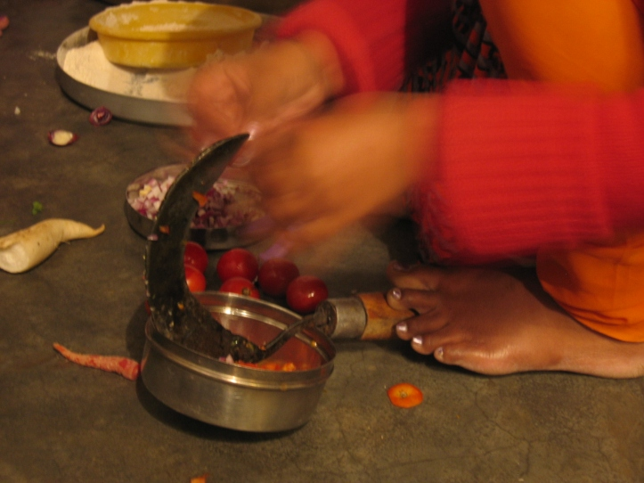 Woman in rural India cutting vegetables on the floor
