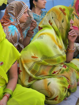 The woman on the left is holding her palu to hide herself from elder men in her in-law family
